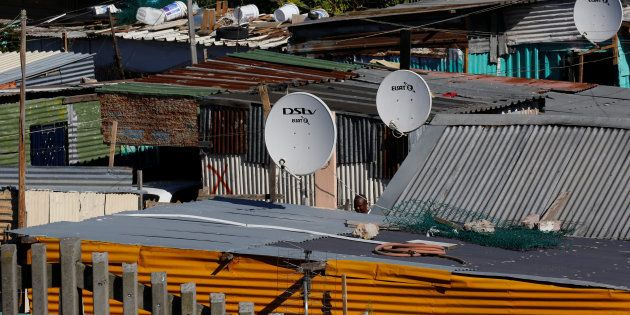 Satellite dishes connect township residents to South Africa's DSTV television network, owned by telecommunications...