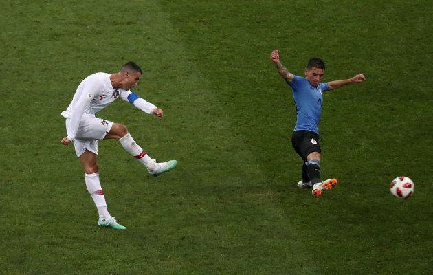 Portugal's Cristiano Ronaldo shoots at goal under pressure from Uruguay's Lucas Torreira during their...