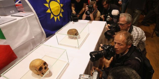 Journalists photograph two of 20 skulls to be taken possession of by a delegation from Namibia at a ceremony...