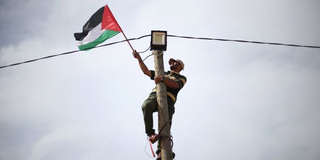 A man hangs a Palestinian flag from an electricity pole near the border with Israel in southern