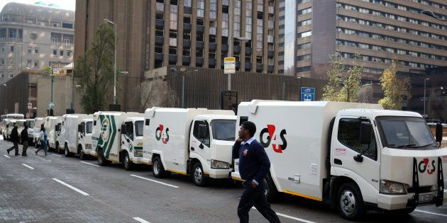 A cash-in-transit worker walks past armoured vehicles parked on the street in Johannesburg during a nationwide...
