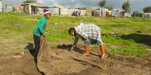 Funeka Sikhafungana and her eight-year-old son pick up a mat after law enforcement officials demolished...