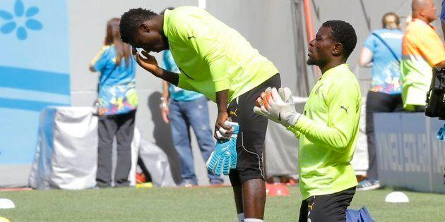 Ghana's goalkeepers, Stephen Adams (L) and Fatawu Dauda (R), pray before a Fifa World Cup 2014
