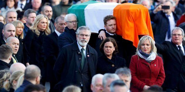 Sinn Feinn President Gerry Adams, centre, walks next to the coffin of Martin McGuinness during his funeral...