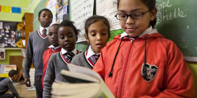 A young school girl reads to her class in a classroom in St Agnes Primary School, Woodstock, Cape Town,...
