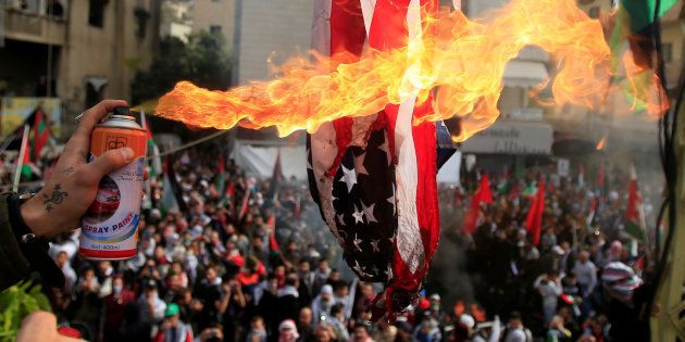 Protesters set a U.S flag on fire near the U.S. embassy in Awkar north of Beirut, Lebanon December