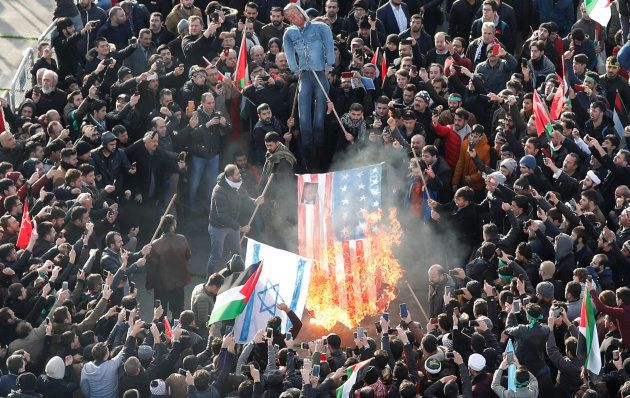 Demonstrators set U.S. and Israeli flags on fire during a protest against U.S. President Donald Trump's...