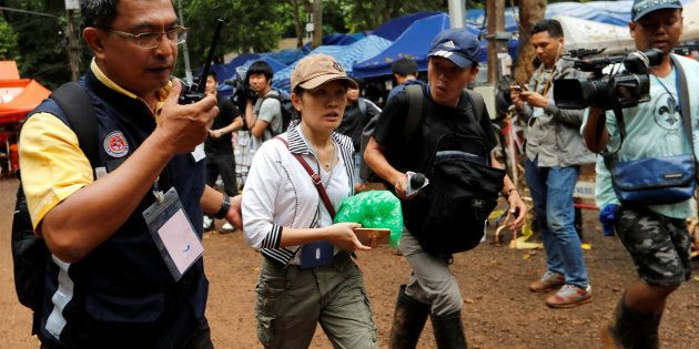 A family member walks outside the Tham Luang cave complex, where 12 schoolboys and their soccer coach...
