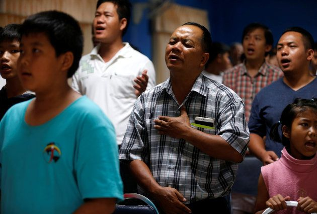 Relatives and friends pray for the 12 schoolboys and their soccer coach tapped inside a flooded cave,...