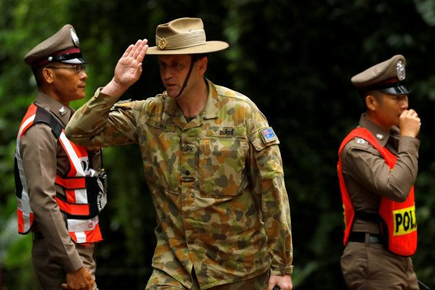 Australian military personnel gestures outside the Tham Luang cave complex, where 12 schoolboys and their...