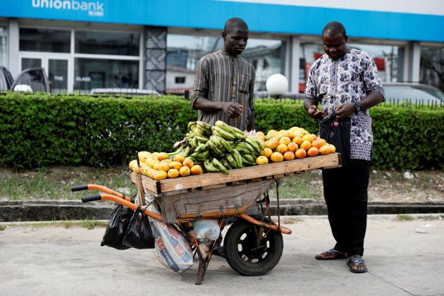 A man selling fruits in a wheelbarrow attends to a customer in front of a bank along a road in Ikoyi...