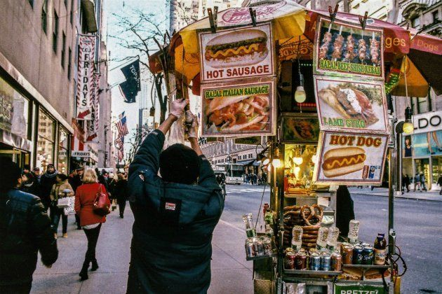 A hot dog cart vendor screws in a new lightbulb on to his fast food cart on 5th Avenue in Manhattan,...