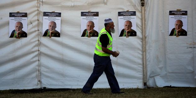 A worker walks past posters bearing the face of anti-apartheid activist Ahmed Kathrada, who was sentenced...