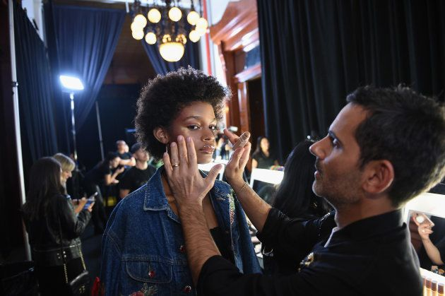 A model has her makeup done with Fenty Beauty products backstage at the FENTY PUMA by Rihanna Spring/Summer...