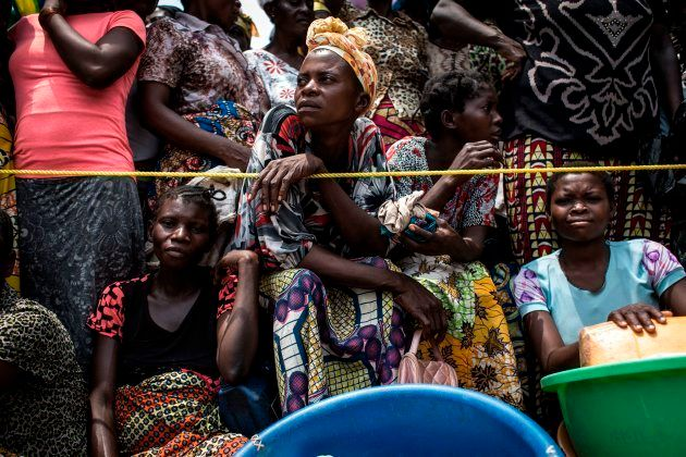 A Congolese woman looks on while people wait for their ration of food to be handed out at a food distribution...