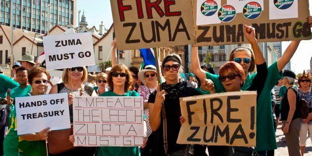 Protestors hold up placards reading 'Fire Zuma' during a demonstration of supporters of the Save South...