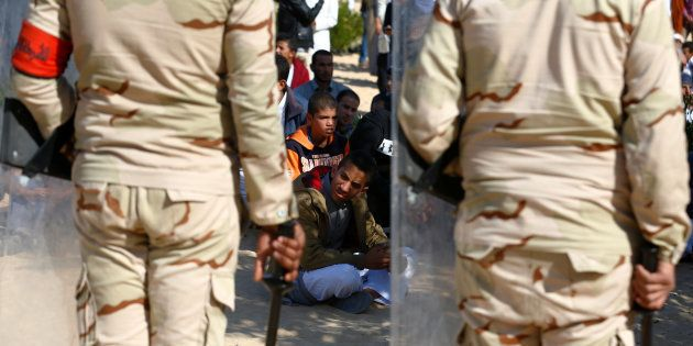 Military officers secure worshippers outside Al Rawdah mosque during the first Friday prayer after the...