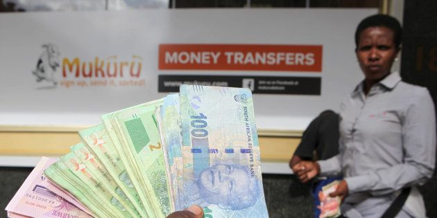 An forex dealer offers bond notes and South African Rand outside a bank in the central business district...