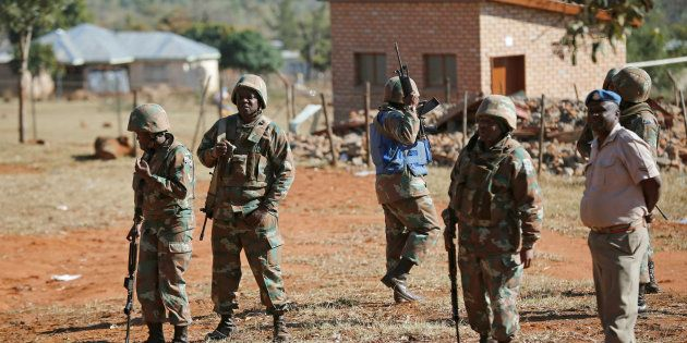 Members of the South African National Defence Force (SANDF) keep watch at a school used as a polling...