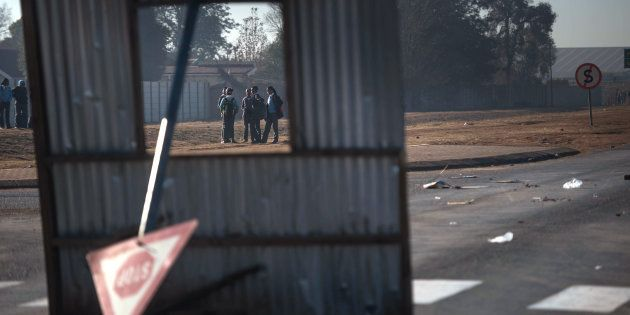 Protesters are framed through an improvised barricade blockading an intersection during a service delivery...