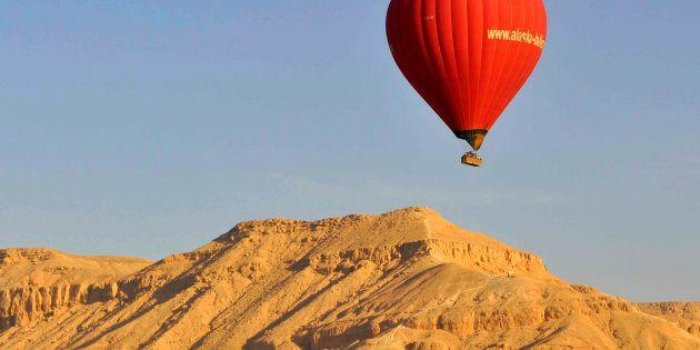 A hot air balloon flies over Luxor on April 21,
