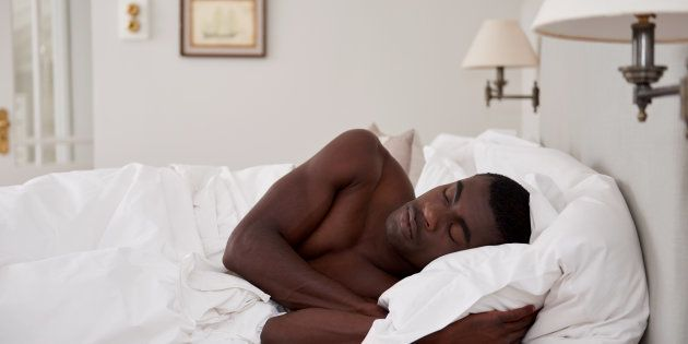 peaceful african black man sleeping comfortably in bed at