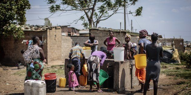 People collect water at a water point in the 'compound' township on the oustkirts of Lusaka on November...
