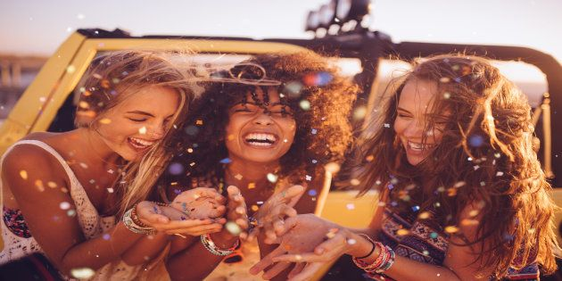 Afro girl and her friends on a road trip together blowing colourful