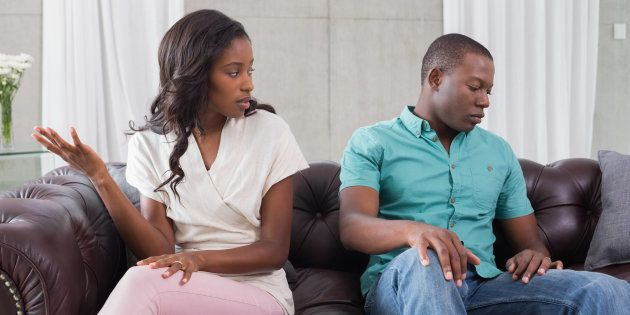 Couple having an argument on the couch at home in living