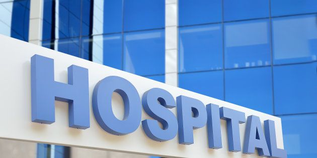 Hospital building sign closeup, with sky reflecting in the glass. 3d