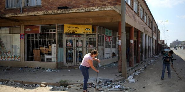 Locals clean up after over-night looting, when protesters took to the streets to demonstrate the killing...