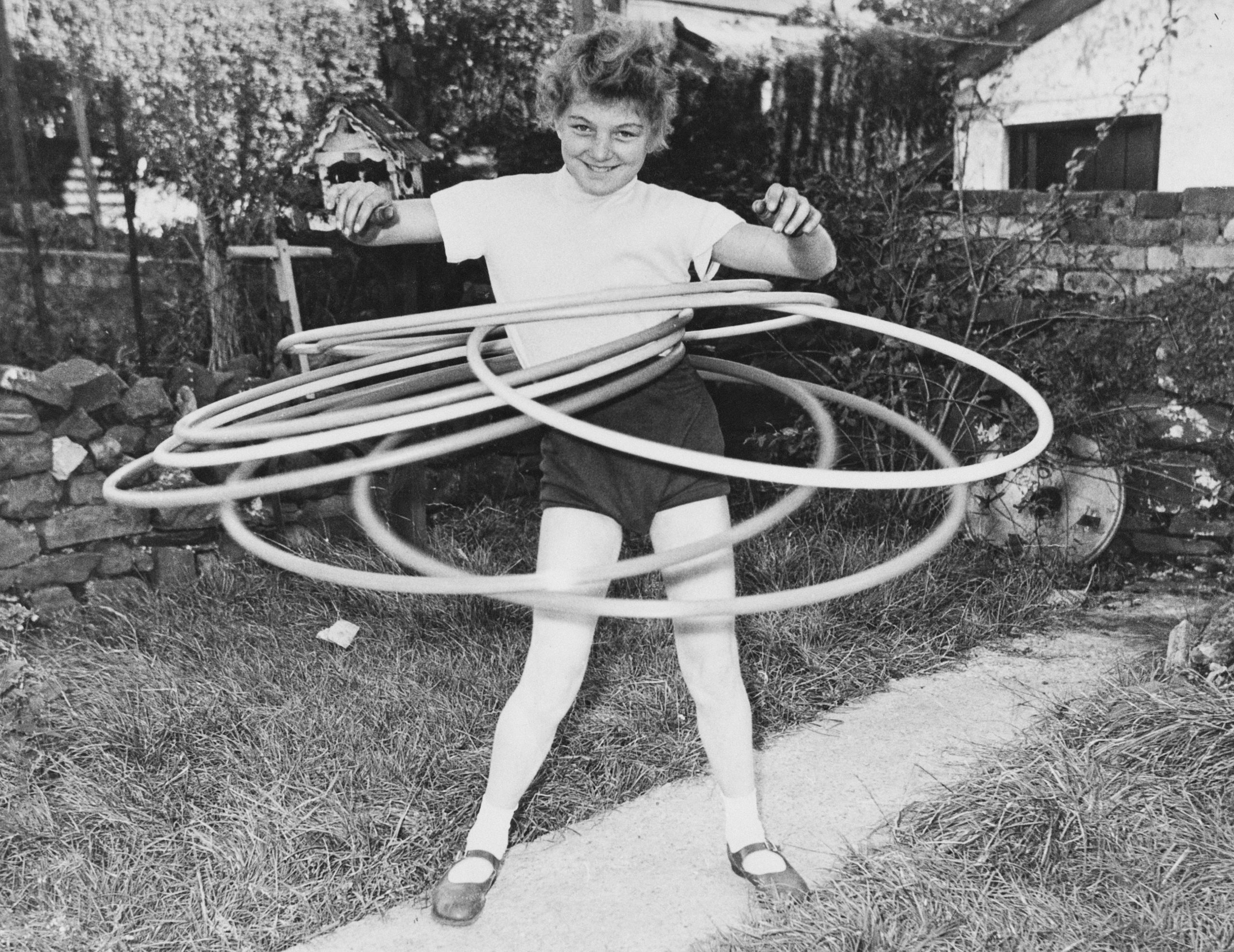 11-year-old Ann Evans of Aberdare, Wales, the world toy hoop marathon champion, keeps seven hoops twirling simultaneously, No