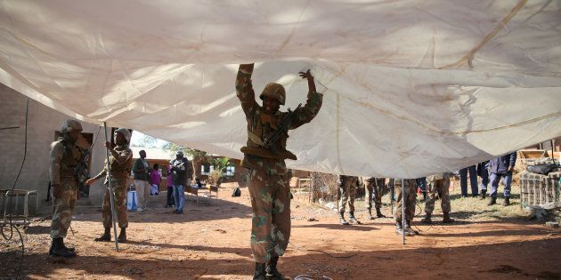 A member of the South African National Defence Force (SANDF) helps set up a tent to be used as a poling...