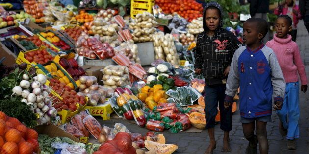 Children walk past a vegetable stall in Soweto July 23,