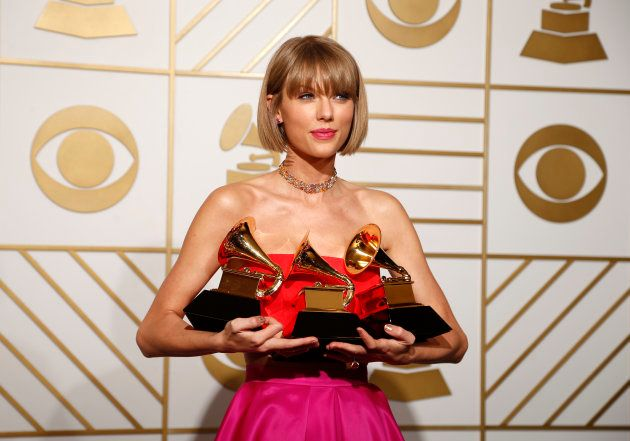 Singer Taylor Swift poses backstage with her awards for Best Music Video for