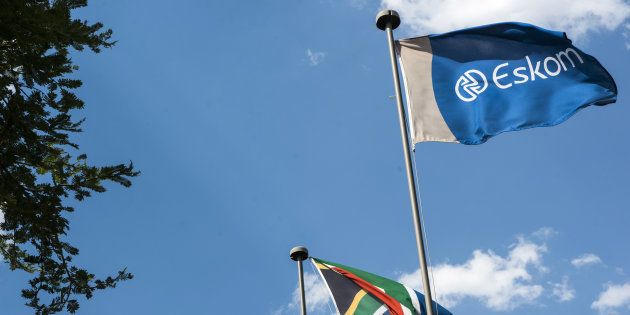 An Eskom flag flies alongside the South African national flag outside the state-owned utility's headquarters...