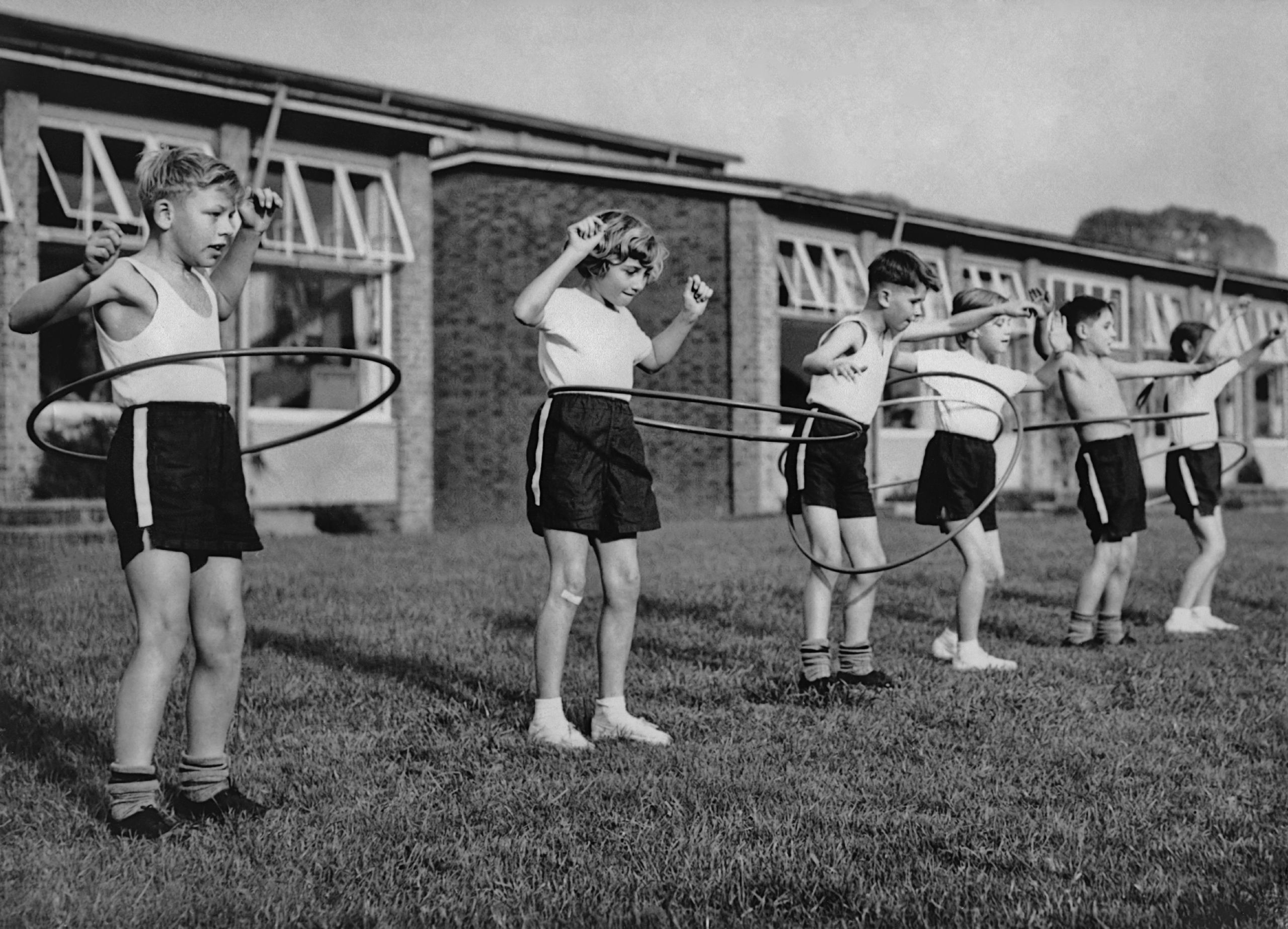 A group of six children play with hoops in a circa-1960s hoop class.