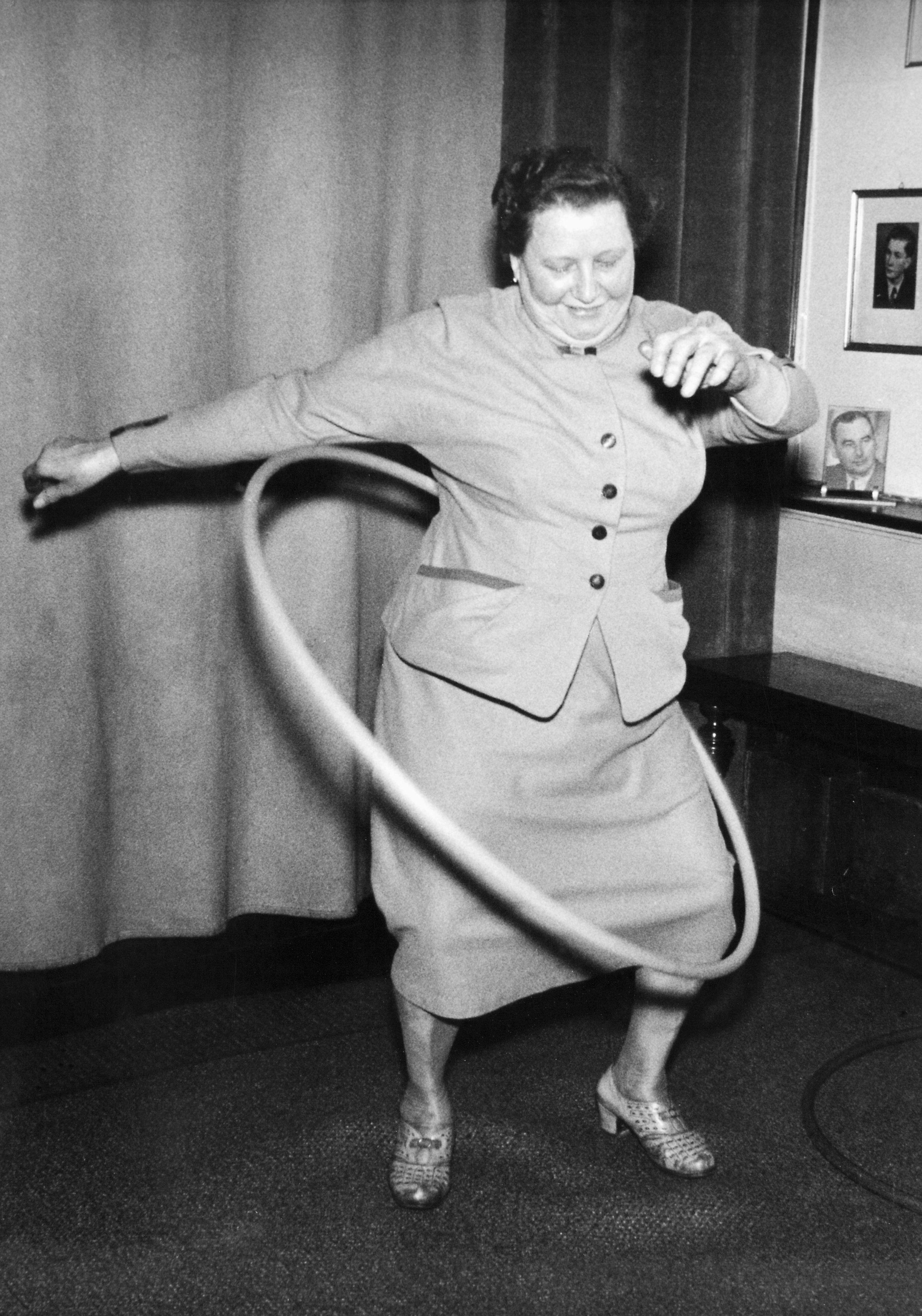 A European woman tries out a toy hoop, circa 1958.