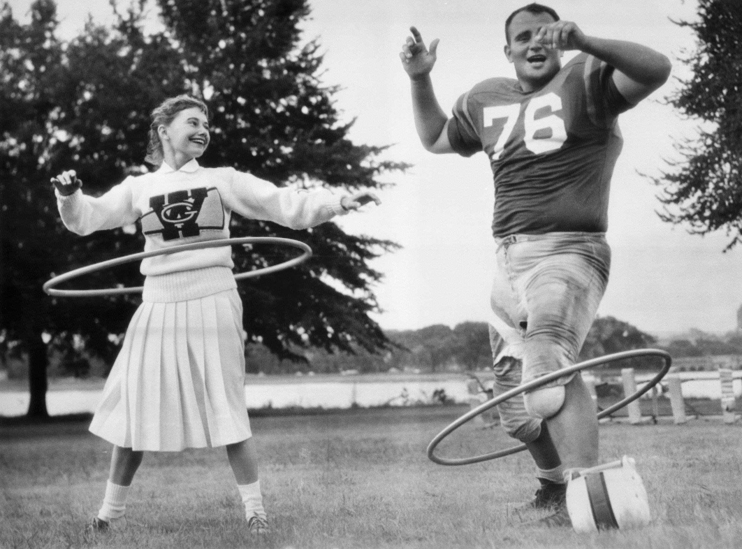 George Washington University cheerleader Anne Sneeringer unsuccessfully attempts to coach Ed Rurbach in the art of spinning a
