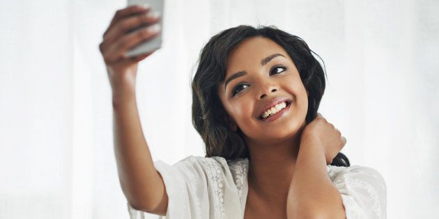 Shot of a beautiful young woman taking a selfie while relaxing in her