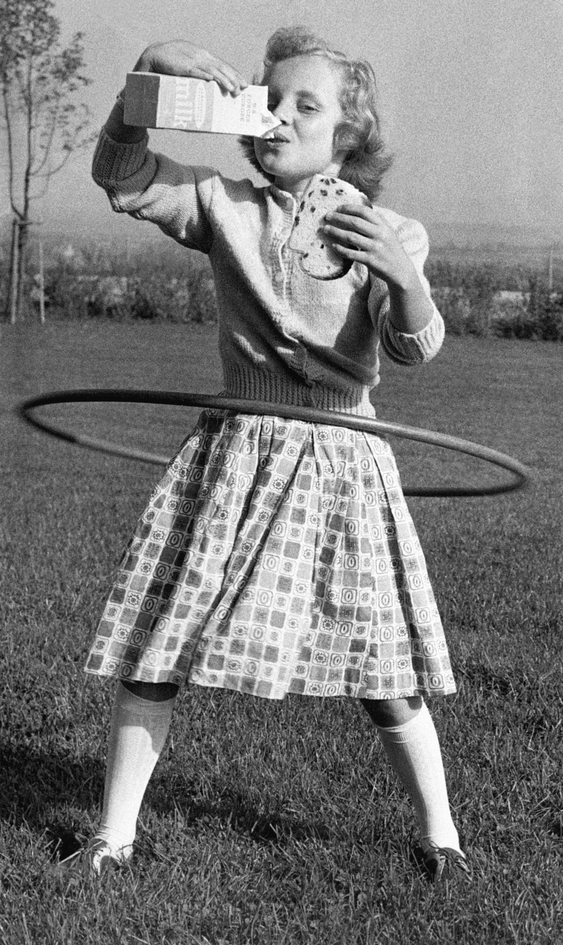 Mimi Jordan, 10, drinks milk and holds a sandwich while hooping.