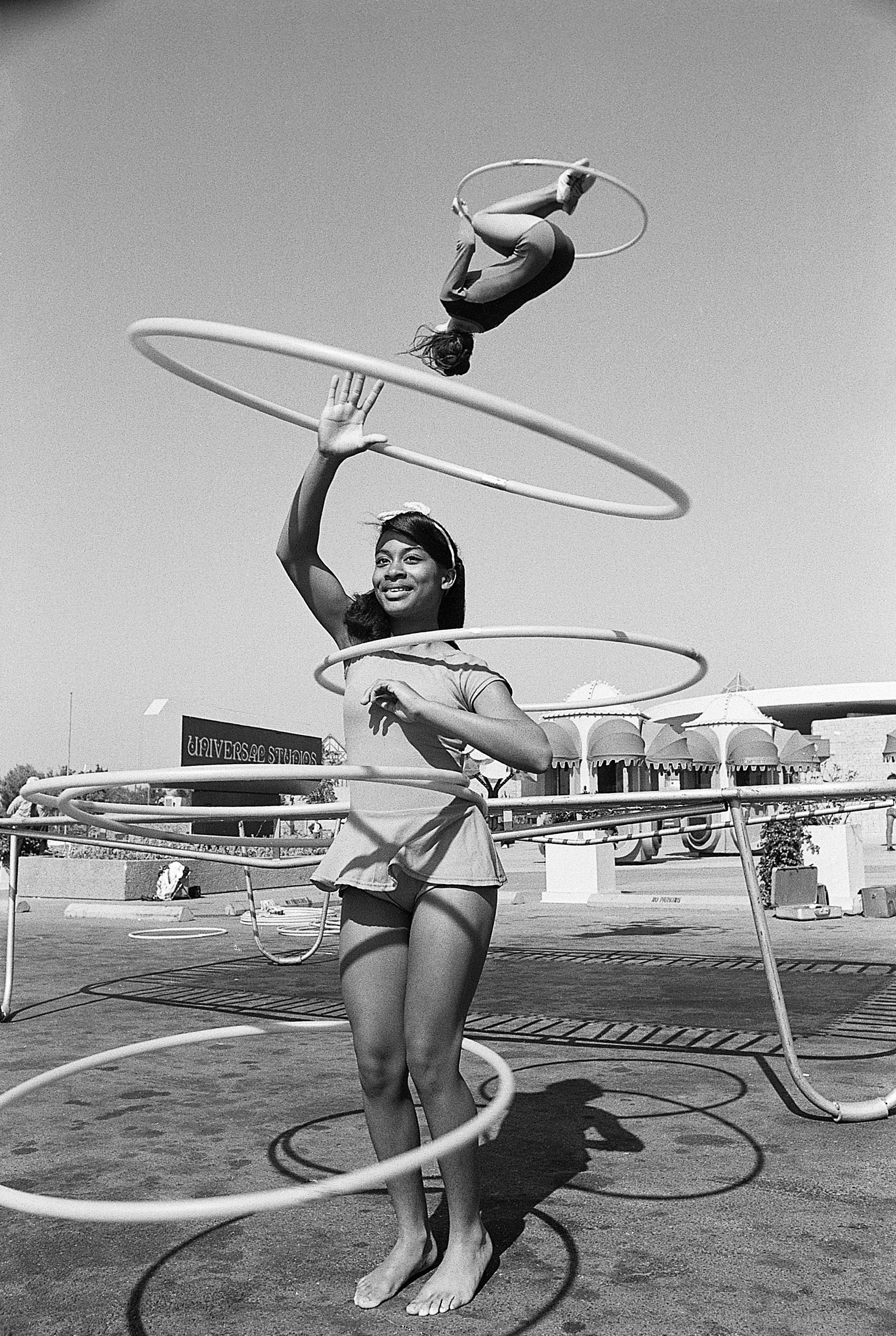 National hula hoop champion Sandra Gaylord spins her hoops in 1972, as world professional trampoline champion Judy Johnson do
