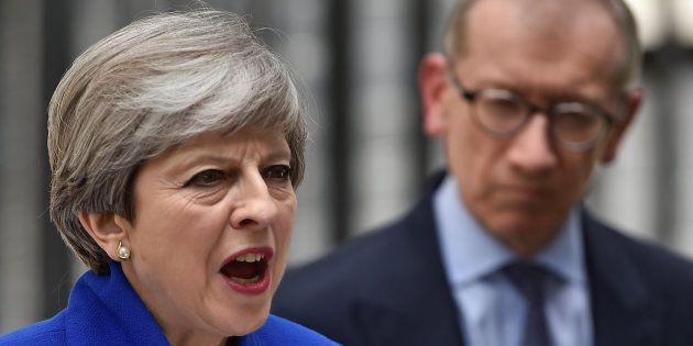 Britain's Prime Minister Theresa May addresses the country as her husband looks on after Britain's election...
