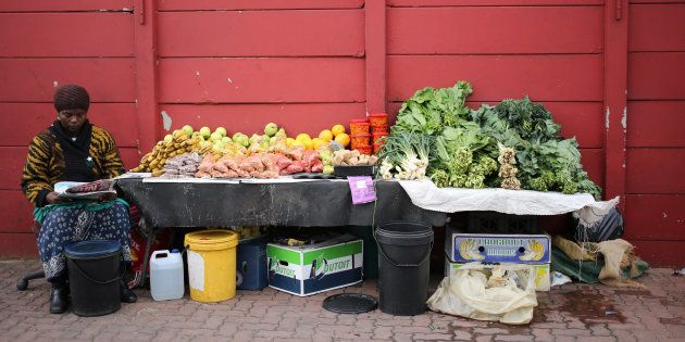 A street vendor waits for customers as she sits in front of her fruit and vegetables stall in Johannesburg,...