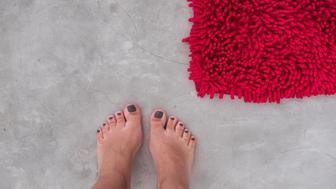 Women feet on a gray concrete floor with red rug fluffy carpet from above. Modern minimal industrial bedroom or bath details