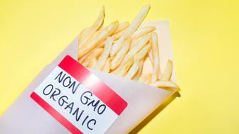 Conceptual food image of french fries: bad food, junk food, fast food, french fry.   Label says Non GMO (Non Genetically Modified) Organic.