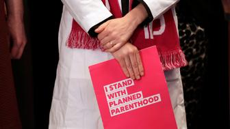 "Dr. Erin Berry, Washington State Medical Director for Planned Parenthood of the Great Northwest and the Hawaiian Islands, holds a folder as she listens at a news conference announcing a lawsuit challenging the Trump administration's Title X ""gag rule"" Monday, Feb. 25, 2019, in Seattle. The rule issued last Friday would impact federal funding for reproductive health care and family planning services. (AP Photo/Elaine Thompson)"