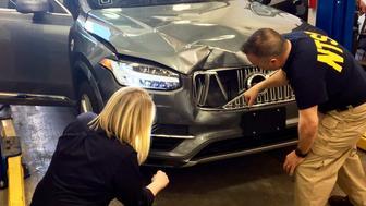 ARCHIVO- Esta foto del 20 de marzo del 2018 proveída por la Junta Nacional de Seguridad del Transporte de Estados Unidos muestra a investigadores examinando un vehículo autónomo de Uber que atropelló y mató a una mujer en Tempe, Arizona.  (Junta Nacional de Seguridad del Transporte vía AP)