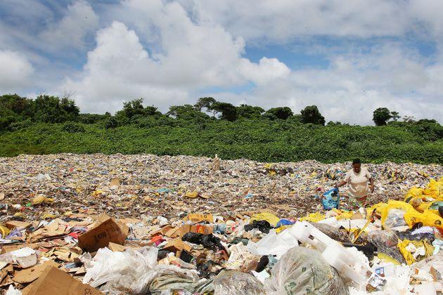 ボウファのゴミ廃棄場でリサイクルできる物を探す女性