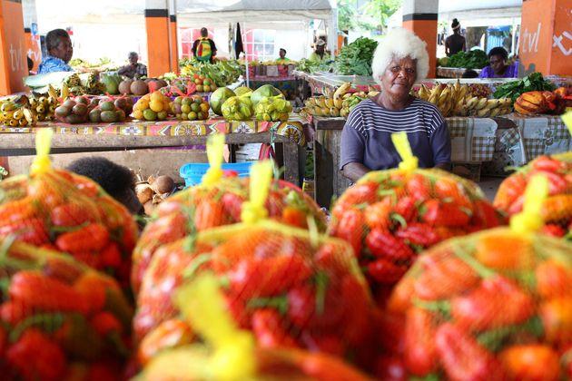 市場で野菜や果物をプラスチックネットで売っている女性
